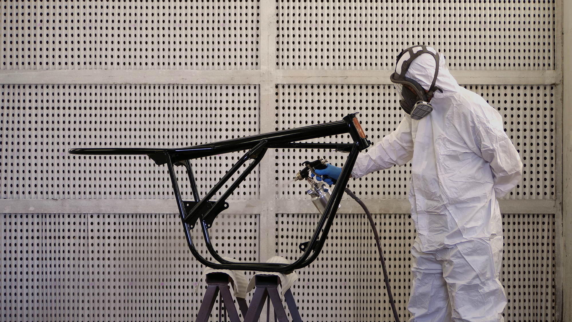 Person wet paint finishing on bike frame